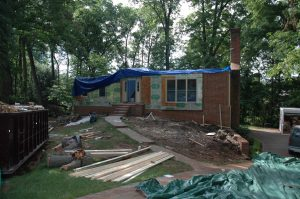 A house without a roof is covered in blue tarps and insulation during the storm damage restoration process