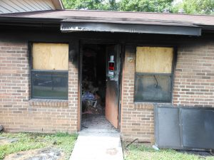 home with boarded up windows and fire damage to front door