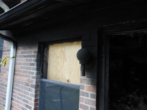 board installed on window of fire damaged home