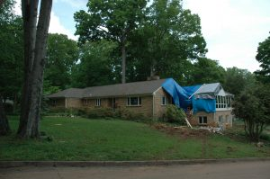 Blue tarps cover storm damage to a brick home's roof and sunroom wing.