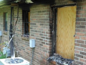 windows boarded up due to fire damage in home